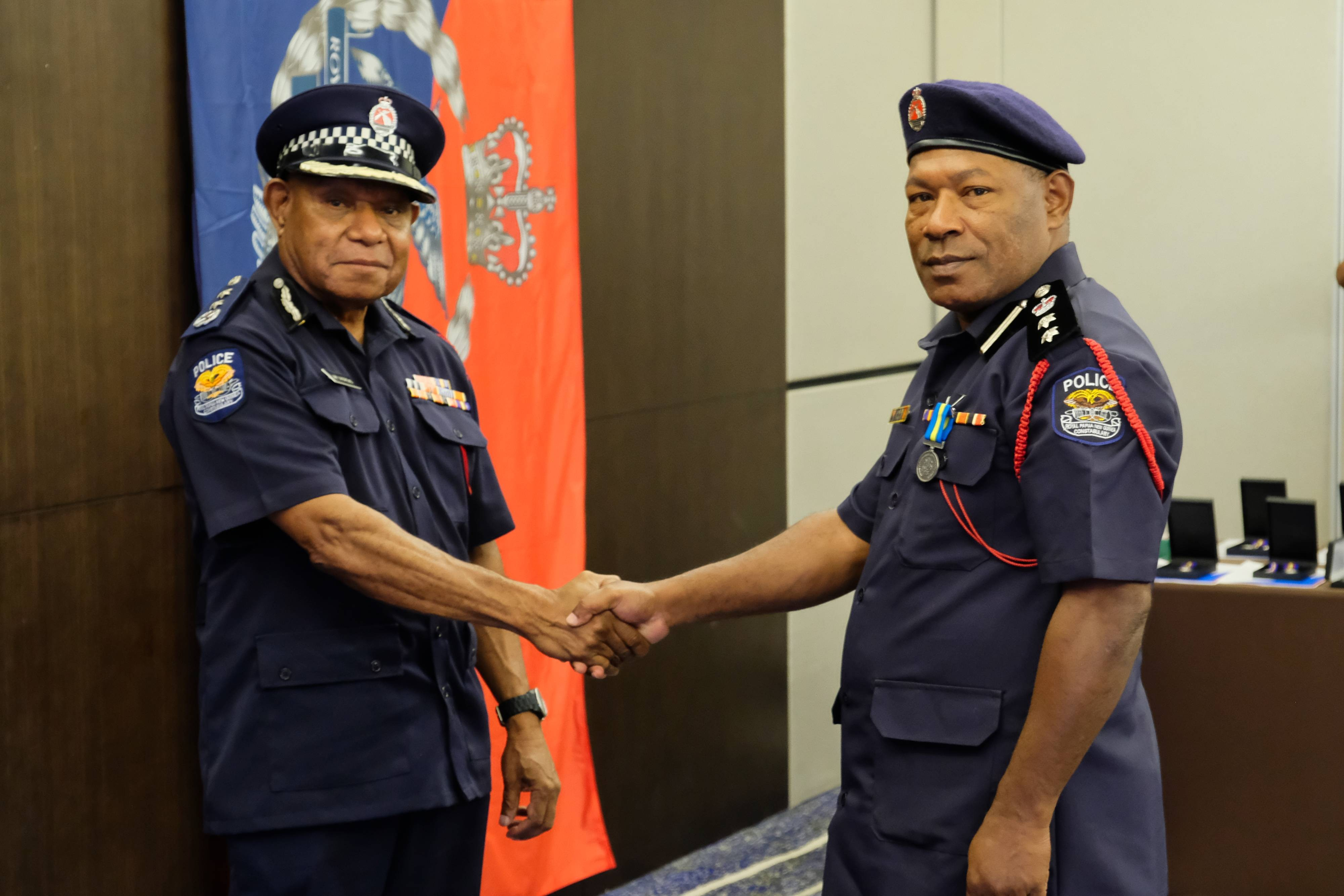 Deputy Commissioner and Chief of Police Operations presenting the Royal Solomon Islands Police's International Law Enforcement Cooperation Medal to Chief Superintendent John Kolopen, Director of the RPNGC Community Policing Directorate