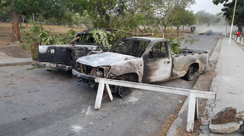 Burnt UPNG vehicles used to barricade the road leading into the main Waigani campus.