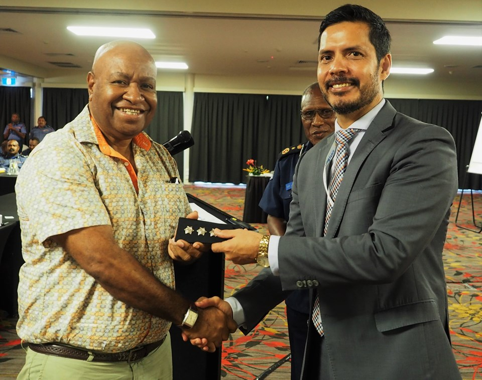 Detective Senior Sergeant Apollos Terry being conferred with the rank of inspector by Police Minister Bryan Kramer, with Police Commissioner Gari Baki in the background