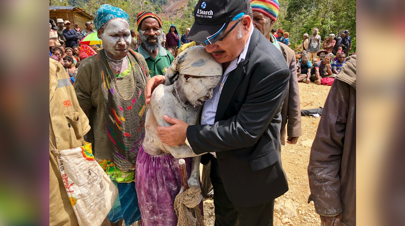 Prime Minister Peter O'Neill hugging an earthquake survivor