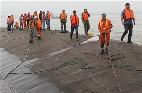 Rescuers save a survivor from the overturned passenger ship